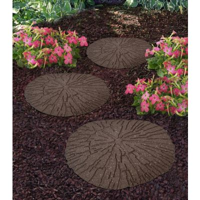 Three cracked earth log stepping stones arranged as a path through leaves and two pink flowered plants
