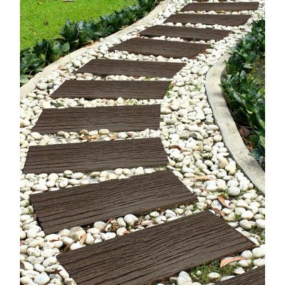 A meandering path of 10 railroad style stepping stones on a bed of white pebbles through a garden