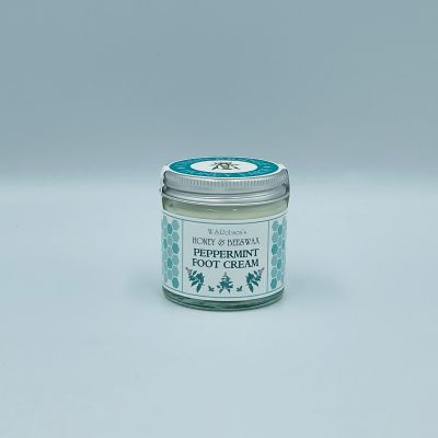Screw top glass jar of honey and beeswax peppermint foot cream wrapped with a branded sticker, white background.