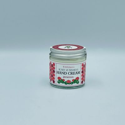Screw top glass jar of honey and beeswax hand cream wrapped with a branded sticker, white background.