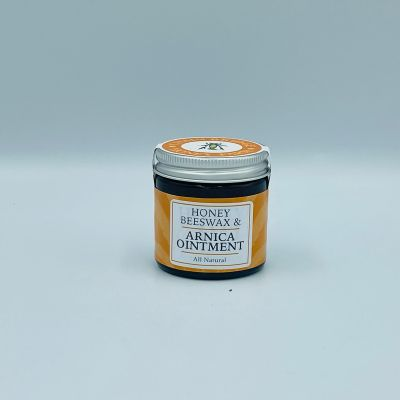 Screw top glass jar of honey and beeswax arnica ointment wrapped with a branded sticker, white background.