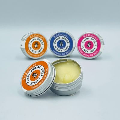 A row of three Chain Bridge honey and beeswax lip balms in a small tins with a branded stickers, also an open tin in front showing the balm inside, white background