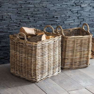 Two square baskets, one filled with logs sat on the floor against a grey slate wall.